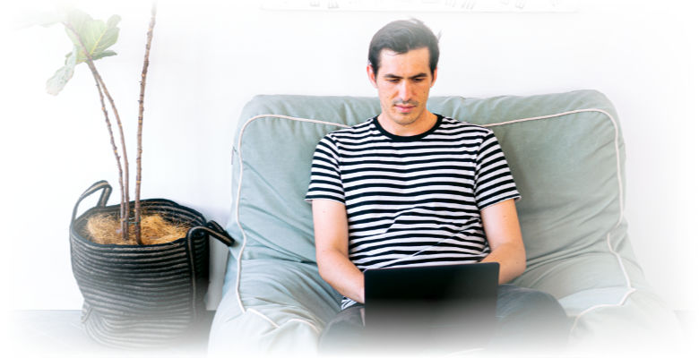 guy cozy on sofa with laptop